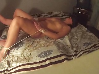 Naked slave lays on the bed as she gets head