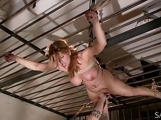 Busty naked babe enjoys bondage and BDSM spanking her pussy