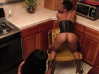 Femdom lesbians having fun in the kitchen with a strapon
