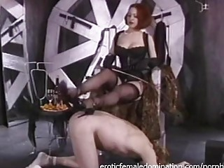 Redhead mistress is punishing her male slave in the dungeon